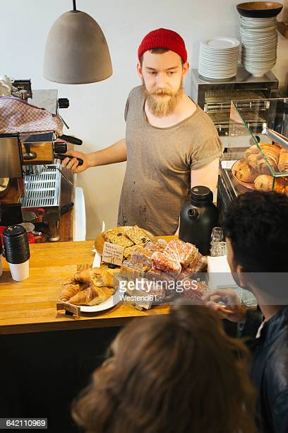 People ordering at cafe counter