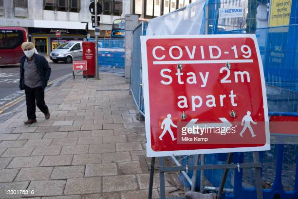 People out and about visiting the shops pass a sign to stay 2m apart in the City Centre as tier three / very high alert level of the Coronavirus tier...
