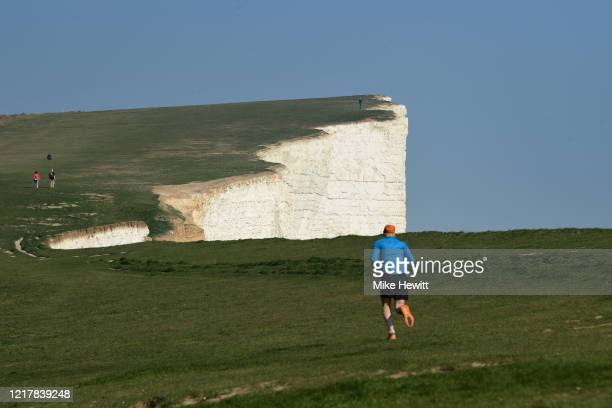 People out exercising on Beachy Head on April 09, 2020 in Eastbourne, United Kingdom. There have been around 60,000 reported cases of the COVID-19...