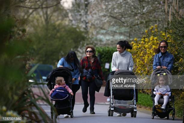 People out for a walk in the warm weather in Regent's Park in London on March 29 as England's third Covid-19 lockdown restrictions ease, allowing...