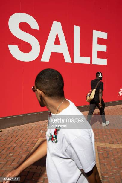 People out shoppin walk past a large scale sale sign in white lettering on a red background outside HM a major high street clothing retail shop in...