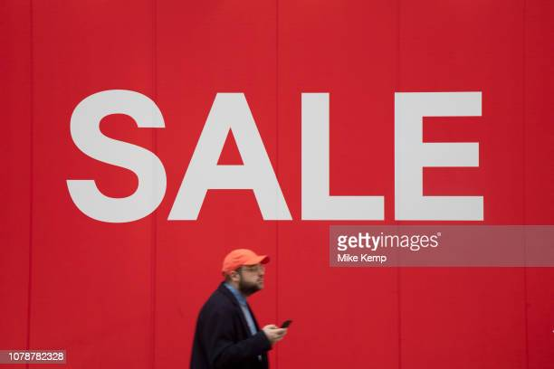 People out shopping on Oxford Street walk past large scale January sale  signs in red and 15cb165e4