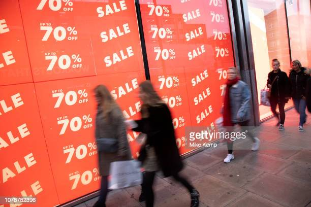 People out shopping on Oxford Street walk past large scale January sale signs in red and white for major high street clothing retail shops on 7th...