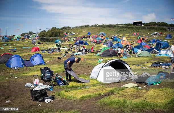 People pack away tents as festival goers leave the Glastonbury Festival 2016 at Worthy Farm Pilton on June 26 2016 near Glastonbury England The...