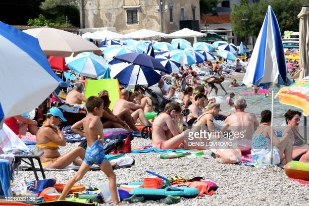 People pack the beach as they sunbathe and swim in Moscenicka draga near Croatia's western town of Rijeka on Adriatic sea on July 10 2020 The number...