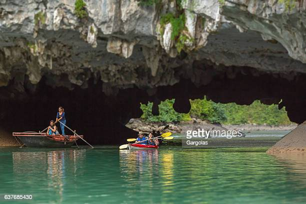 People paddle aboard kayaks to enter a cave, Halong bay