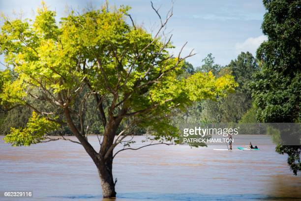 People paddle across Logan River which was affected by floodwaters caused by Cyclone Debbie in North MacLean Brisbane on April 1 2017 Flooded rivers...