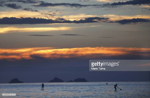 People paddle in the Atlantic ocean during the first sunset of 2018 along Ipanema beach on January 1 2018 in Rio de Janeiro Brazil Fireworks were...