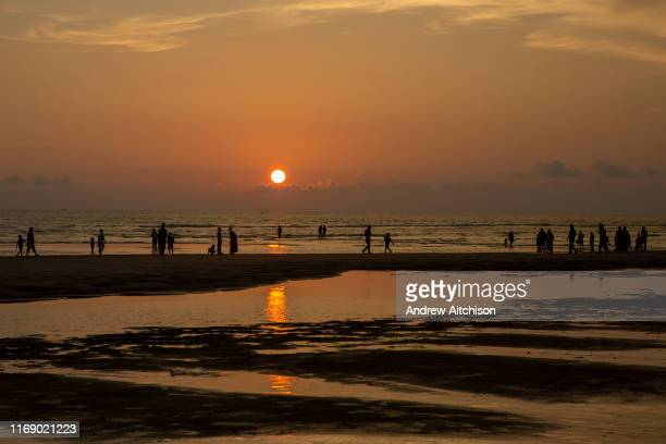 People paddle in the sea and walk along the sandy shoreline of Laboni Beach looking out to the Bay of Bengal in Cox Bazar Chittagong Division...