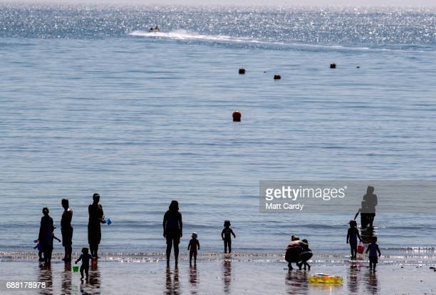 People paddle in the sea as they enjoy the warm weather on the beach in Lyme Regis on May 25 2017 in Dorset England Parts of the UK are currently...