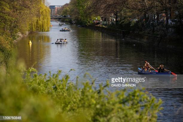 People paddle inflatable boats and canoes along the Landwehr canal in Berlin's Kreuzberg district as the sun shines on Easter Sunday April 12 2020...