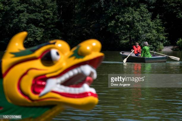 People paddle rowboats as a dragon boat sits in The Lake at Central Park before a traditional dragon boat awakening ceremony July 18 2018 in New York...