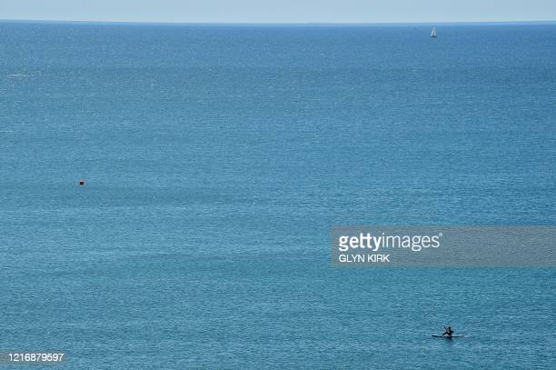 People paddleboard a SUP inthe sea off Saltdean beach near Brighton on the south coast of England on June 2, 2020 following a further relaxation of...