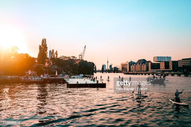 people paddleboarding in spree river by city against clear sky during sunset - berlin stock-fotos und bilder