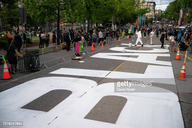 """People paint a Black Lives Matter mural on East Pine Street in the so-called """"Capitol Hill Autonomous Zone"""" on June 10, 2020 in Seattle, Washington...."""