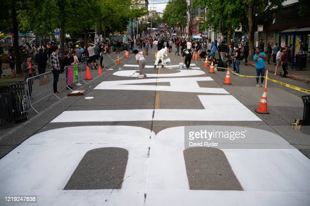 People paint a Black Lives Matter mural on East Pine Street in the socalled Capitol Hill Autonomous Zone on June 10 2020 in Seattle Washington The...