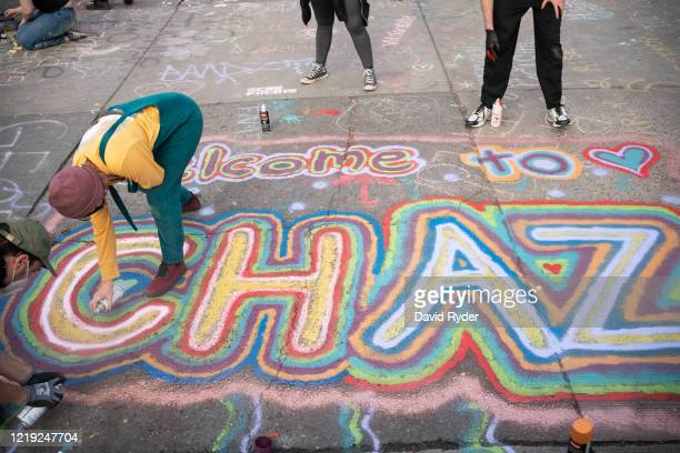 People paint an acronym for Capitol Hill Autonomous Zone near the Seattle Police Departments East Precinct on June 10 2020 in Seattle Washington The...