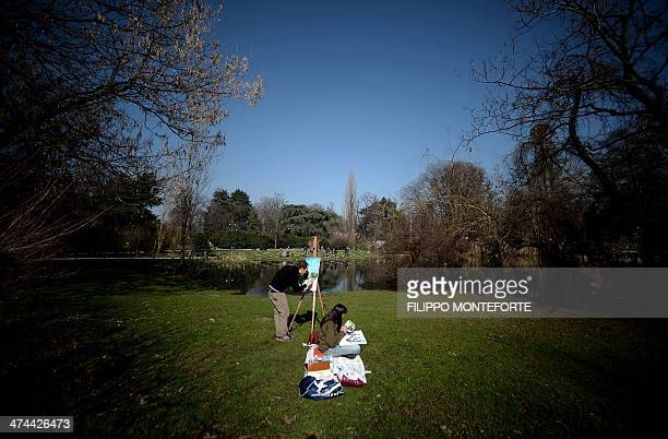 People paint in central Milan's Parco Sempione as they enjoy the warm weather on February 23 2014 AFP PHOTO / Filippo MONTEFORTE