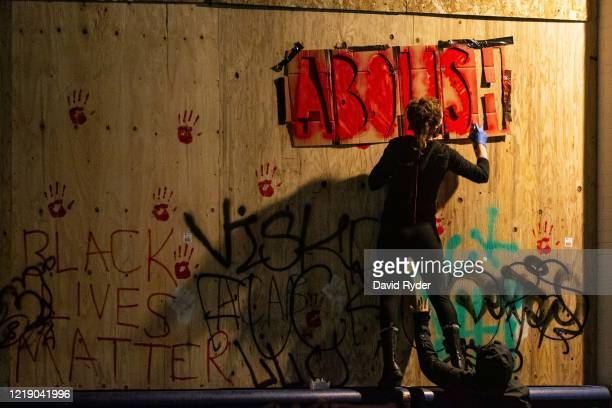 People paint the exterior of the Seattle Police Departments East Precinct on June 9, 2020 in Seattle, Washington. Protests have continued in many...