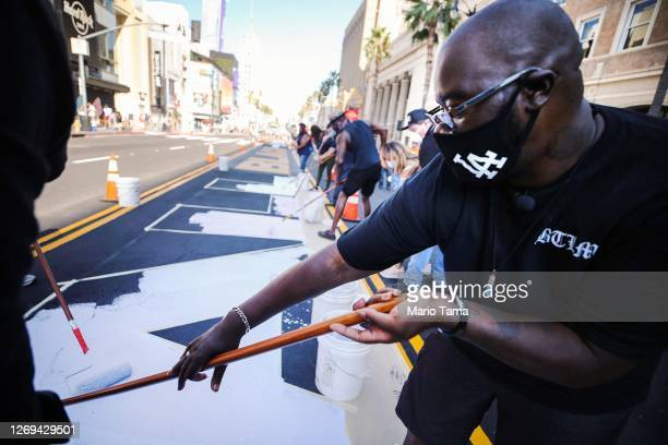 People paint the new permanent 'All Black Lives Matter' mural on Hollywood Boulevard on August 28, 2020 in Los Angeles, California. An original...