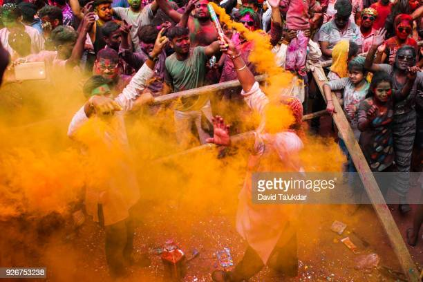 People painted with bright colors dance during the festival of Holi