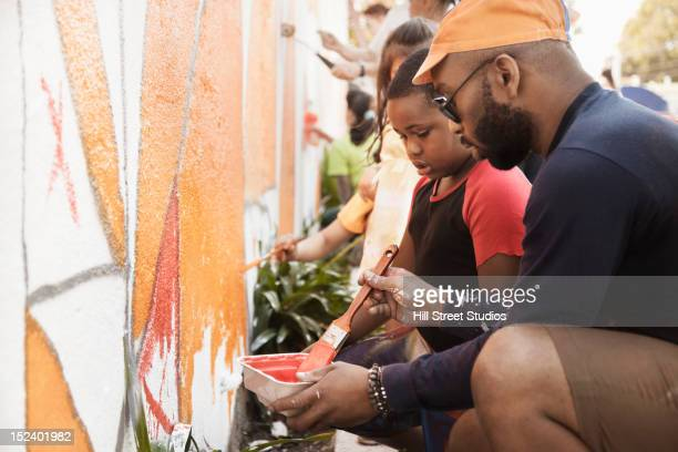 people painting wall together - wall building feature stock pictures, royalty-free photos & images