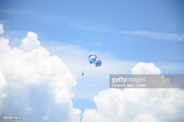 people paragliding against cloudy sky - gliding stock photos and pictures