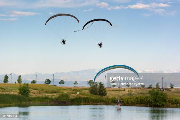 People Paragliding Over River