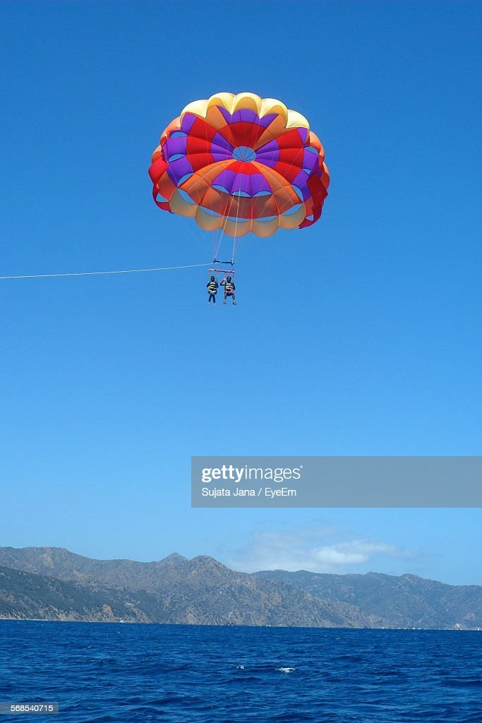 People Paragliding Over Sea Against Blue Sky : Stock Photo