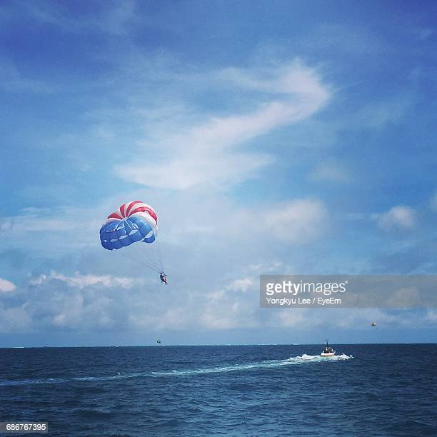 People Parasailing Over Sea Against Cloudy Sky