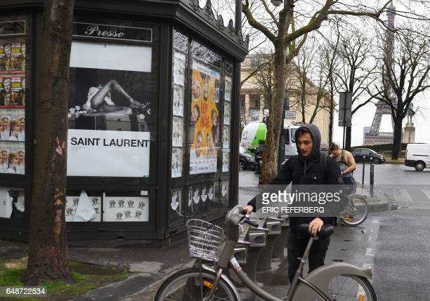 People parks bicycles next to an advertisement for the French luxury fashion brand Yves Saint Laurent on March 6 2017 in Paris A new publicity...