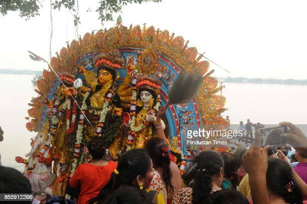 People participate during an immersion process of Goddess Durga idol of Sovabazar Raj Bari which completed 261 years on Vijaya Dashami on September...