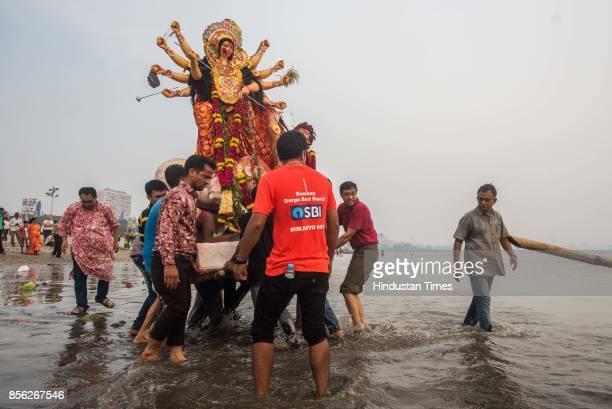 People participate during an immersion process of Goddess Durga idol at Girgaon Chowpatty on September 30 2017 in Mumbai India Vijayadasami is...