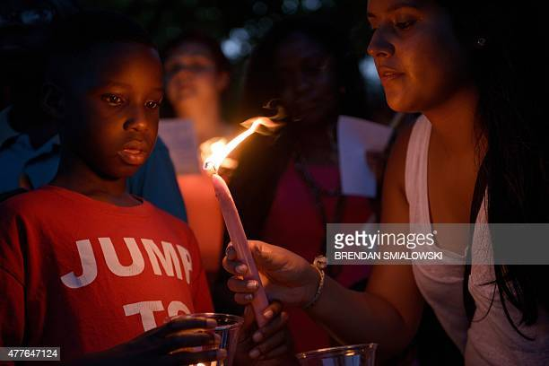 People participate in a candle light vigil at Marion Square near the Emanuel AME Church in Charleston South Carolina on June 18 2015 Police captured...