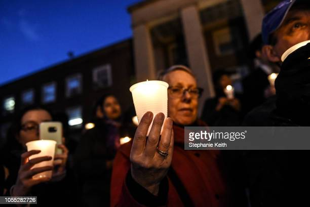 People participate in a candle light vigil in memory of the victims of the mass shooting at the Tree Of Life Synagogue on the steps of Queens Borough...