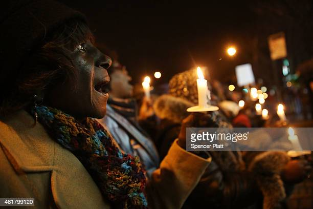 People participate in a candlelight vigil and wreath laying ceremony with the Reverend Al Sharpton at the location where Eric Garner was killed...