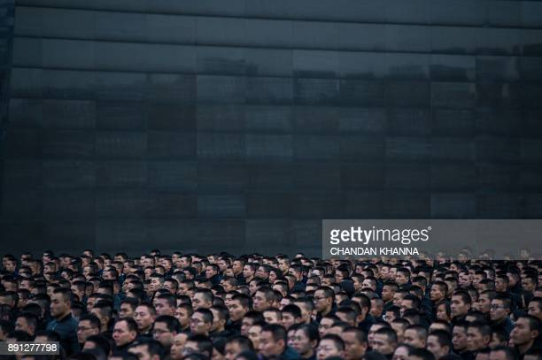 TOPSHOT People participate in a ceremony at the Nanjing Massacre Memorial Hall on the second annual national day of remembrance to commemorate the...