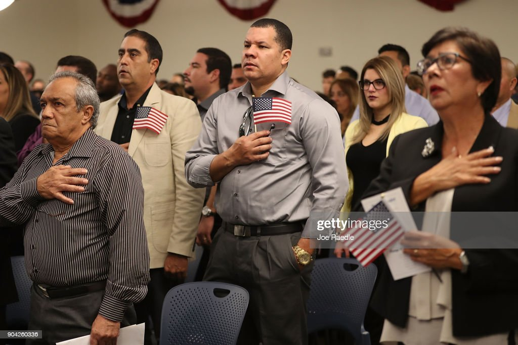 People participate in a ceremony to become American citizens during a U.S. Citizenship & Immigration Services naturalization ceremony at the Hialeah Field Office on January 12, 2018 in Hialeah, Florida. 150 people from different countries around the world took part in the Oath of Allegiance.
