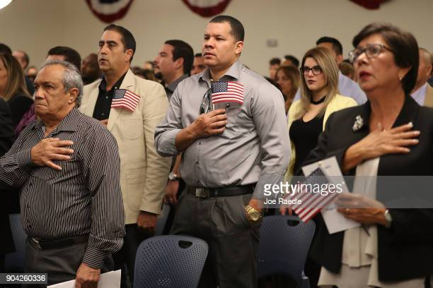 People participate in a ceremony to become American citizens during a US Citizenship Immigration Services naturalization ceremony at the Hialeah...