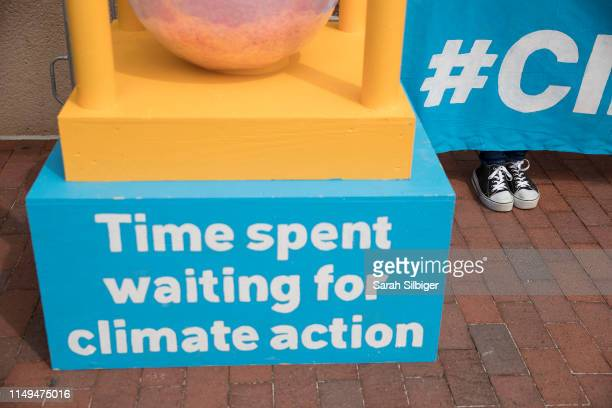 People participate in a demonstration in front of the Democratic National Committee headquarters during a Greenpeace rally to call for a presidential...