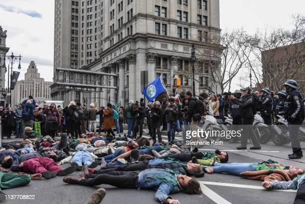 People participate in a diein direct action with a group protest organization called Extinction Rebellion on April 17 2019 in New York City The...