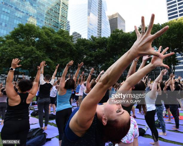People participate in a free outdoor yoga event in Bryant Park in New York City July 12 2018