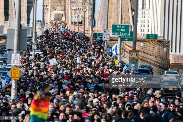 People participate in a Jewish solidarity march across the Brooklyn Bridge on January 5 2020 in New York City The march was held in response to a...