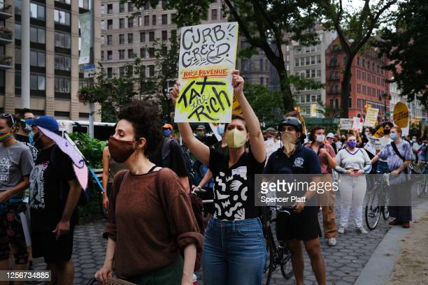 """People participate in a """"March on Billionaires"""" event on July 17, 2020 in New York City. The march, which included a diverse group of activists,..."""