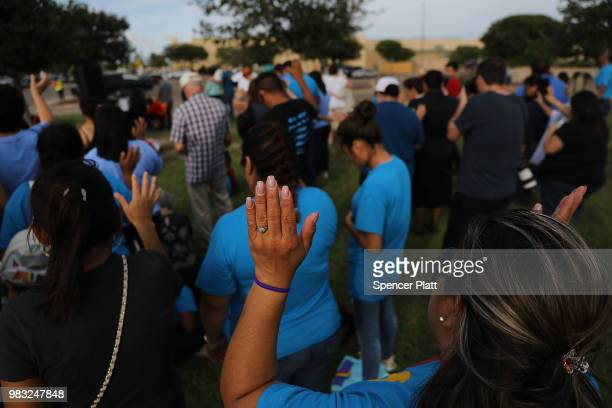 People participate in a prayer vigil in front of Casa Padre, a former Walmart which is now a center for unaccompanied immigrant children on June 24,...