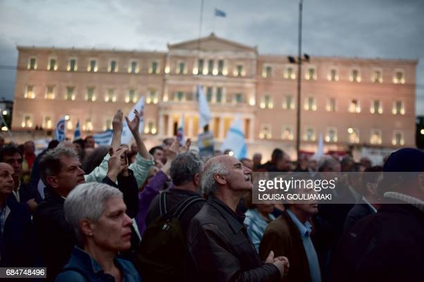 TOPSHOT People participate in a rally outside the Greek parliament in Athens on May 18 during a demonstration on the sidelines of a voting on new...