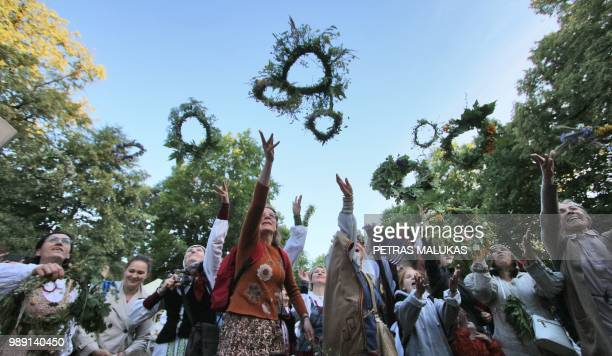 People participate in a traditional Lithuanian summer solstice in Verkiai Park in Vilnius on June 22 2018 Dancing around a blazing fire with garlands...