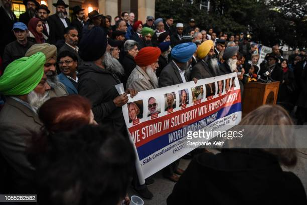 People participate in a vigil in memory of the victims of the mass shooting at the Tree Of Life Synagogue on the steps of Queens Borough Hall on...