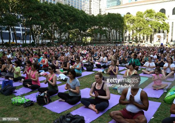People participate in an outdoor yoga event in Bryant Park in New York City July 12 2018