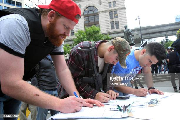 People participating in a guns rights rally sign a petition supporting Washington state Initiative 1621 that would allow people with a concealed...